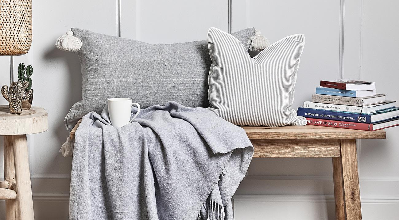 Braune Holzbank mit Kissen, Decke und Büchern im Flur