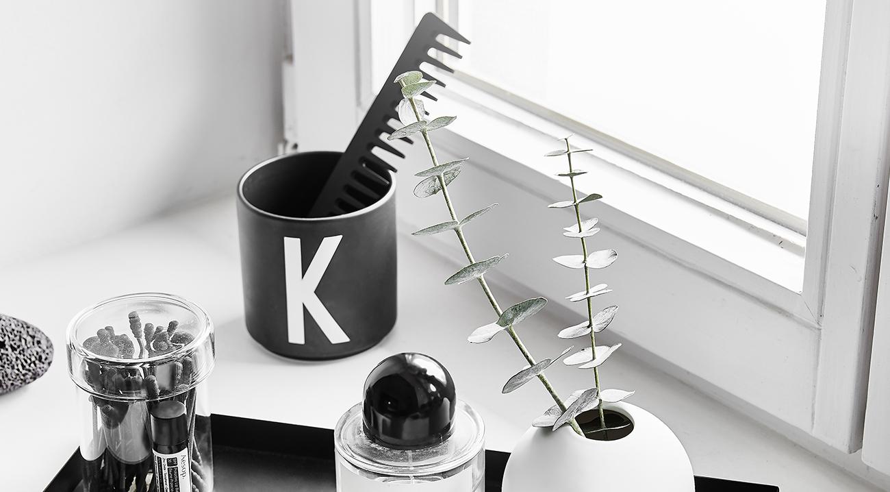 Becher in Schwarz, Weiß mit Buchstabendruck auf dem Fensterbrett