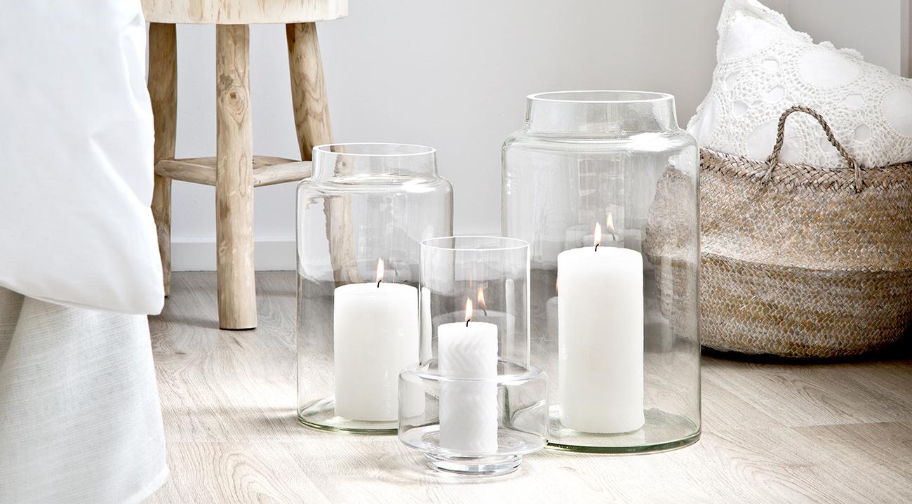 Weiße Kerzen in verschiedenen Größen in Windlichtern