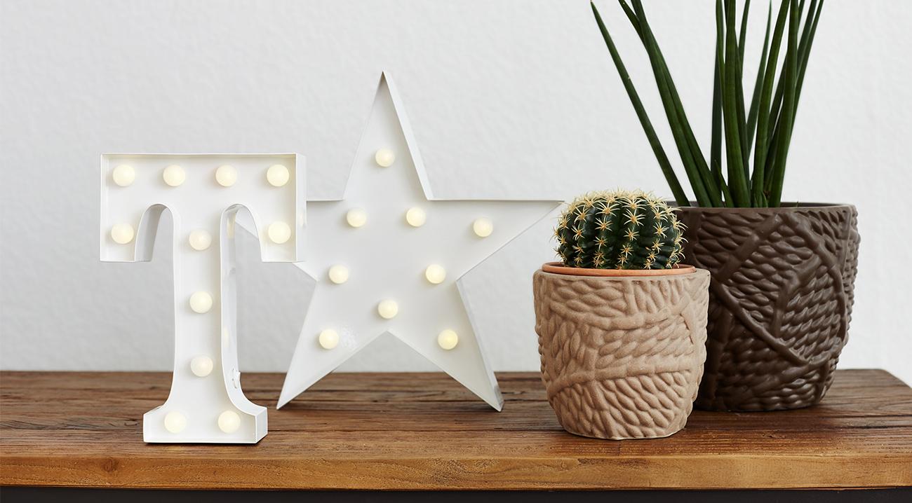 Weiße Leuchtbuchstaben aus Kunststoff auf Kommode