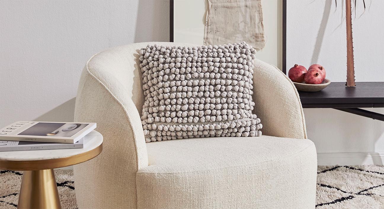 Schönes Kissen Indie in Creme auf einem Sessel