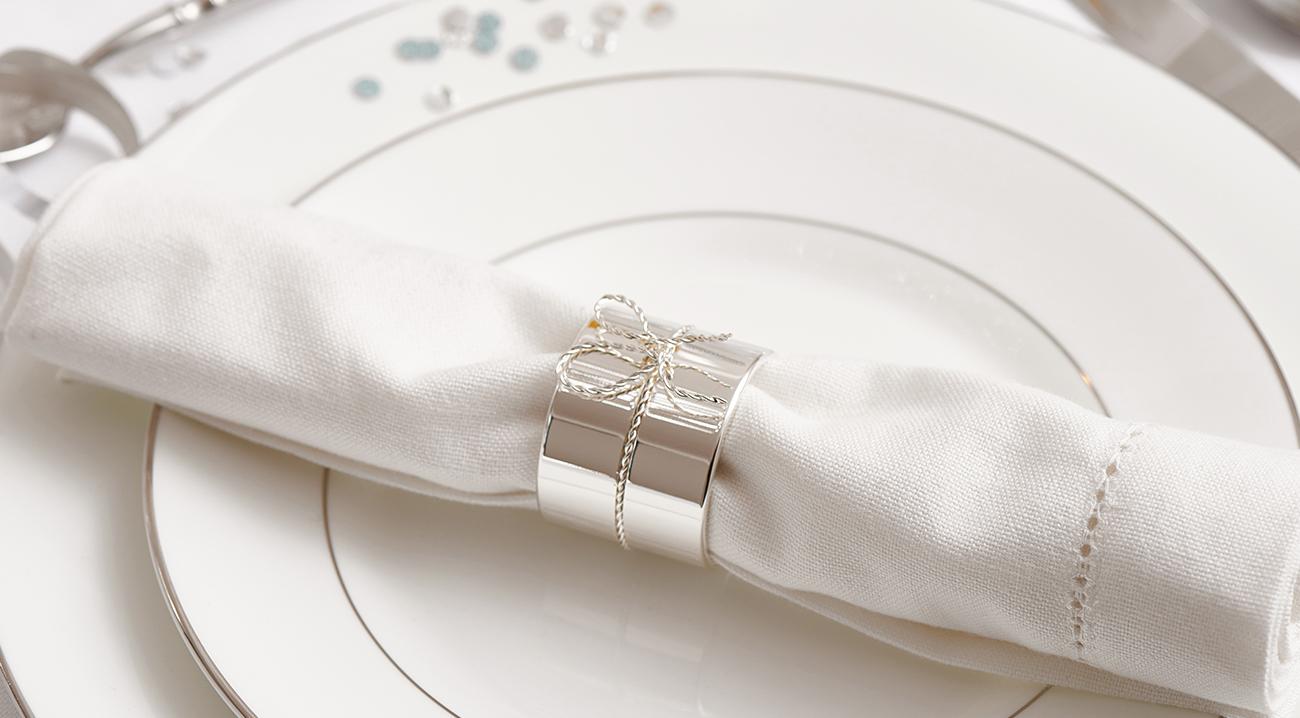 Weiße Leinenserviette auf Porzellanteller mit Serviettenring in Silber
