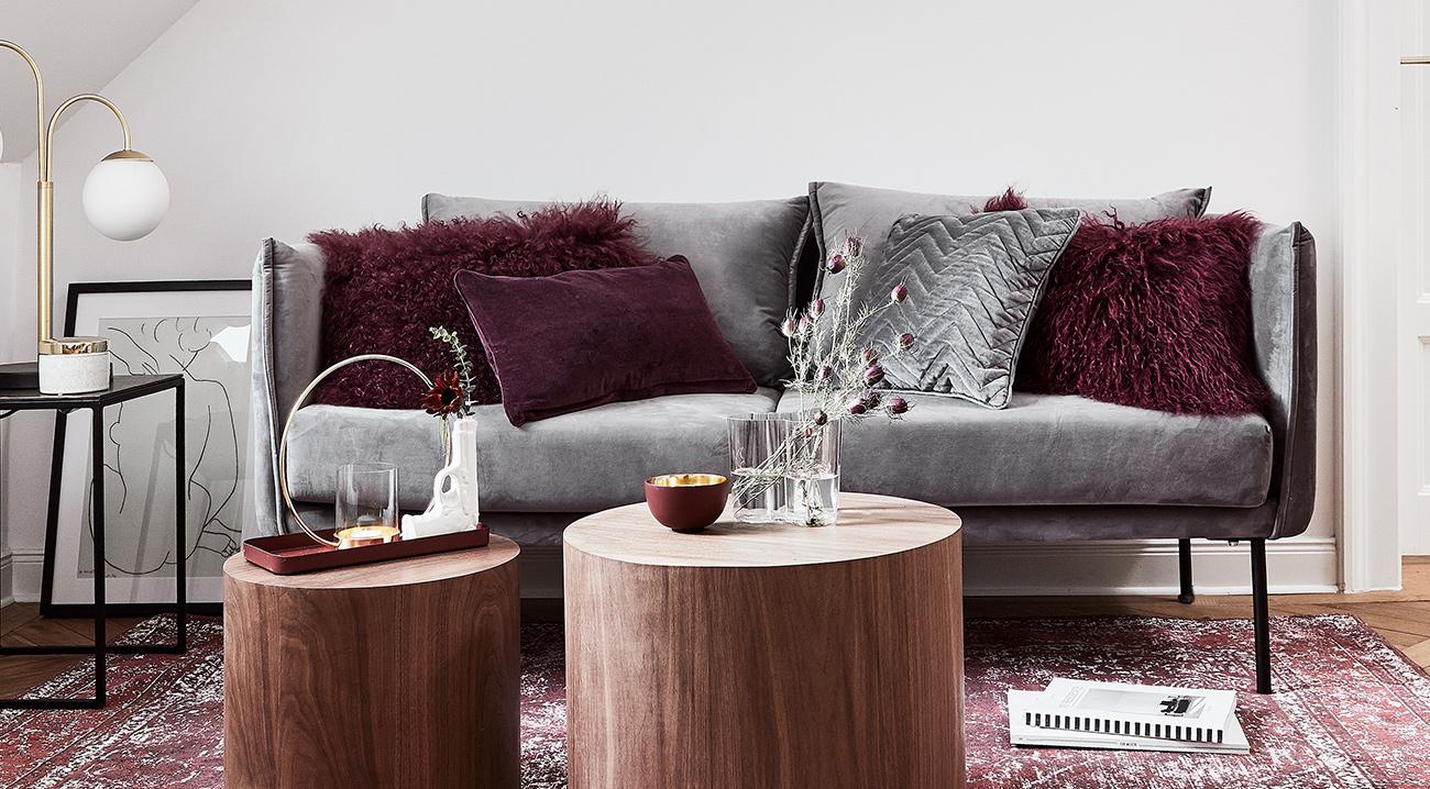 Graues Samt-Sofa im Wohnzimmer mit verschiedenen Dekokissen