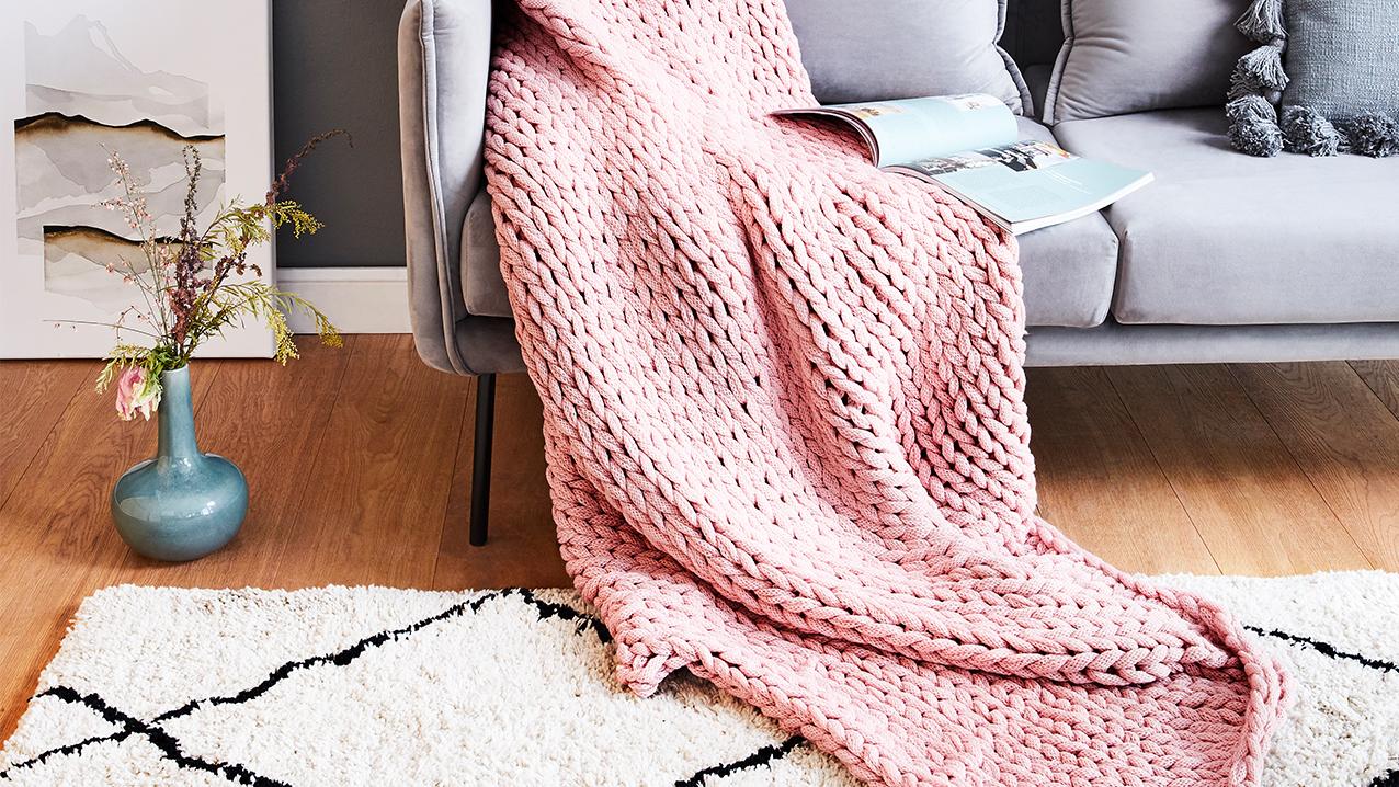 Rosa Sofadecke in Grobstrick auf grauem Sofa