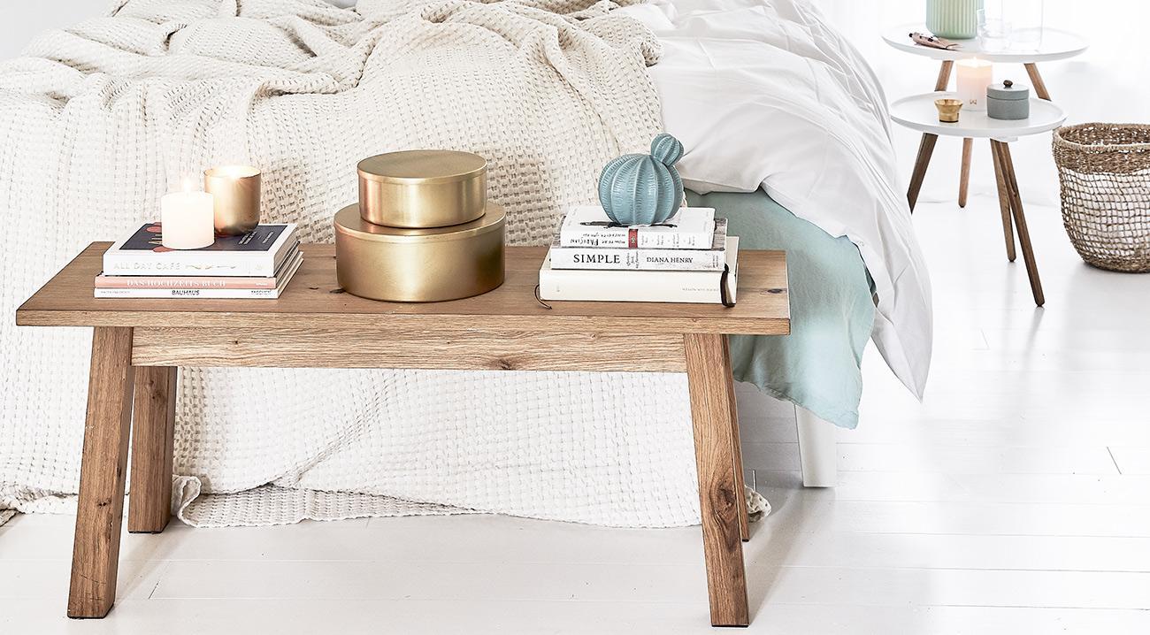 Bank aus Holz vor einem Bett im Schlafzimmer