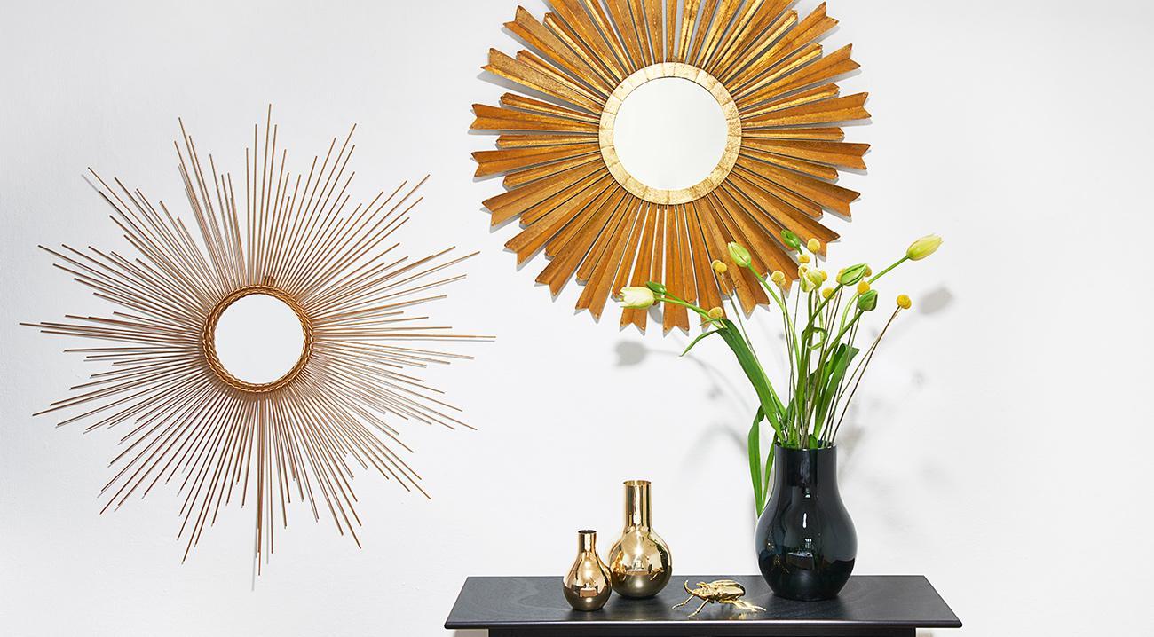 Deko- und Sonnenspiegel in Gold an der Wand