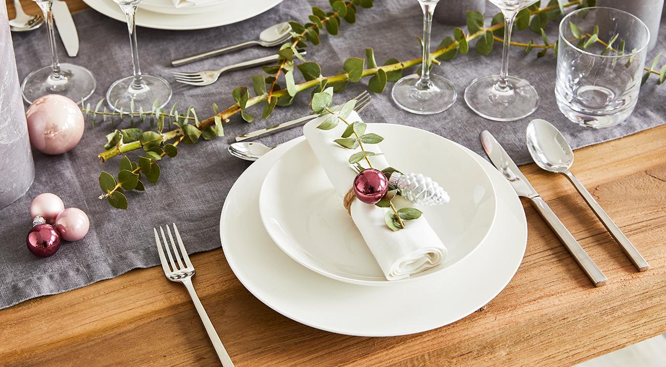 Weißes Geschirr, silbernes Besteck und eine weihnachtliche Tischdekoration