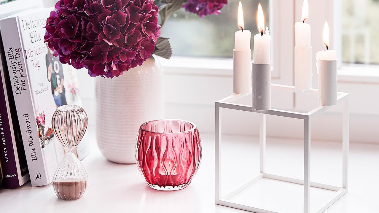 Weißer Kerzenhalter aus Metall auf dem Fensterbrett