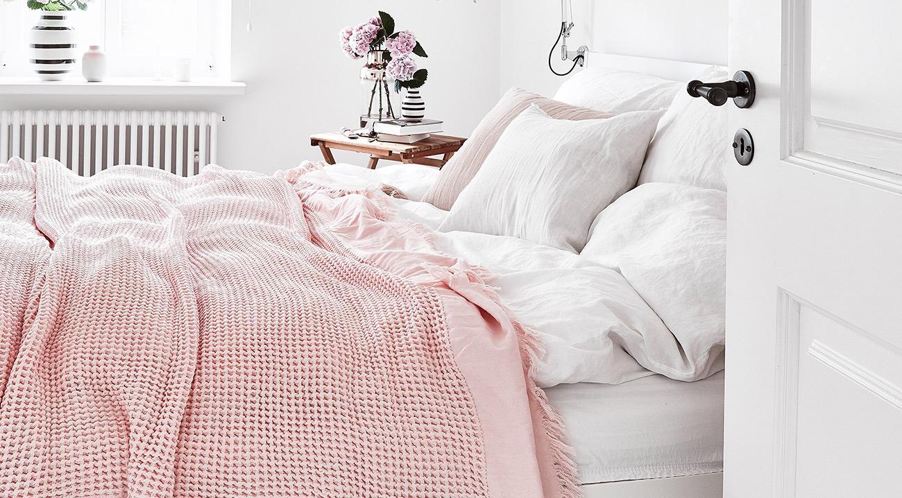 Rosafarbene Tagesdecke aus Baumwolle auf dem Bett