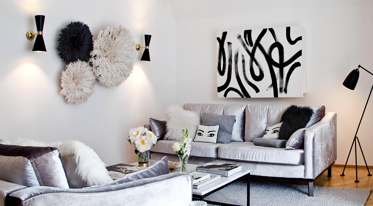 Schwarze Wandleuchten neben Wandobjekten im Wohnzimmer